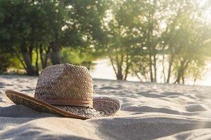 summer travel holidays weekend concept, lady hat on the ocean coast on sand