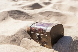 locked treasure case buried in sand on the beach