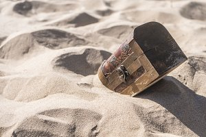 locked treasure chest in the sand on a summer day