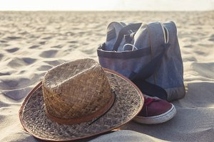 summer hat and bag on the sand of the beach