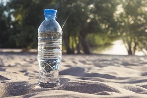 close up bottle with water on the sand on the tropical beach