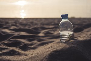 sunset bottle in the sand on the sea coast
