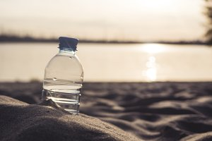 close up bottle with water on the sea coast in sand
