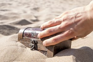 close up hand with treasure chest buried in sand on sea coast beach