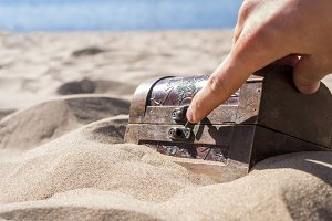 close up hand opens locked treasure chest in sand on a sea coast