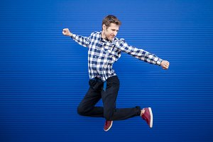 isolated young happy flying man in casual clothes jumps on a blue background
