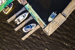 close aerial view of cruise tourist boats floating near the wooden pier in the sea