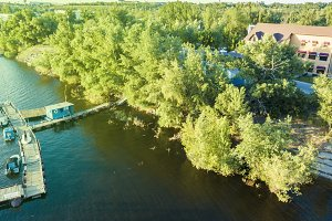 big summer cottage standing on the bank of the river aerial view