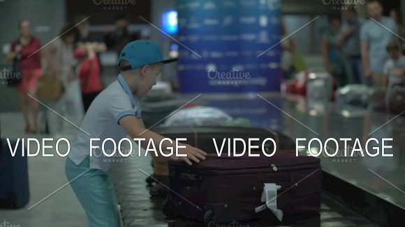 Boy Looking For His Suitcase On Baggage Conveyor Belt At The Airport