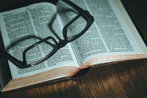 Open Bible with glasses on top