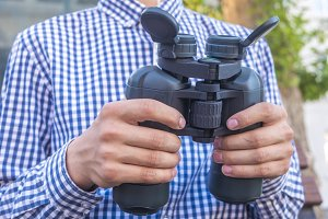 close up person holidng binoculars in front of chest