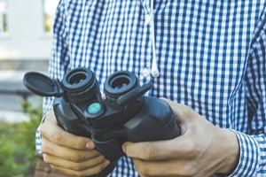 close up view of traveler holding binoculars to find the right way
