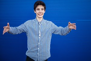 teenager on a blue background going to hug another person