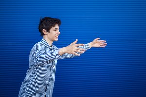 portrait of smiling young teenage boy wants to hug a person