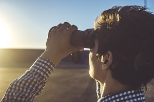 young man looking for the right way with binocular