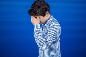 portrait of young man facepalmig on a blue background
