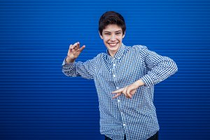 young laughing teenager dancing moves isolated on a blue background