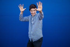 young teenage boy giving high five while dancing on a blue background