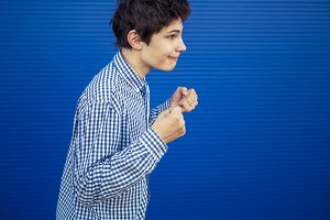 bully concept, young teenage boy at school showing fists on blue background