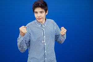 young man showing two fists  isolated on blue background