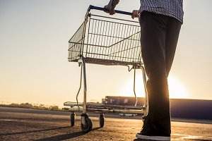 close up person walking with the shopping cart, abstract concept outside