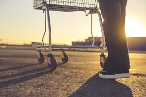 person's legs with shopping cart on the asphalt