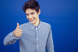 young smiling male teenager showing thumb up on a blue background