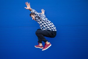 jumping motion of young man on a blue background