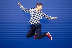 isolated jumping smiling young man on a blue background