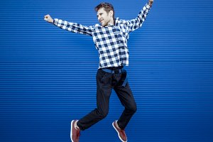 young happy man in casual clothes jumping