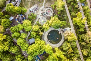 aerial view of amusement park with many trees on a summer day