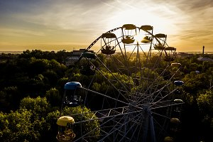 aerial view of ferris wheel in the park during summer sunset in the park between the trees