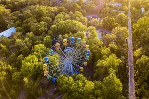 aerial ferris wheel in the park between the trees on a  summer day