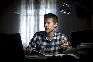 young man doing home task with lots of books and laptop under the lamp