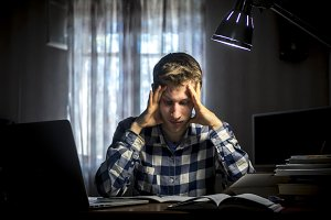 student thinking sitting in the dark room at the table with lamp