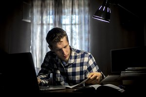 young bearded smiling student doing homework sitting at the table with lamp