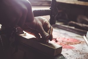 close up man's hand hammering nail into wood in workshop