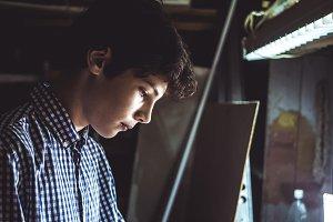 young man in checkered shirt portrait working in dark workshop