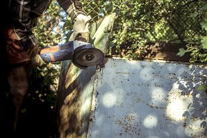 close up grinder cutting metal list outdoor in the garden on a summer day