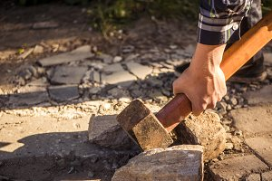 close up hand in shirt holding a hammer and crashing the stone against sun outdoor