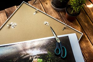 scissors on a photo before putting it into a frame overhead view