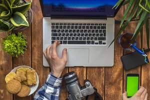 overhead person working at home studio using laptop and smartphone with croma key