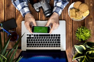 photographer working using phone and laptop on a wooden table