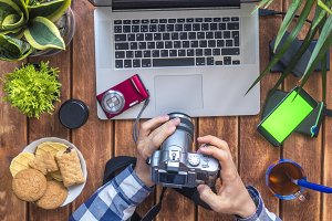 photographer holding camera at his working place with laptop