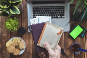hand with passport and wallet before travel trip over working place