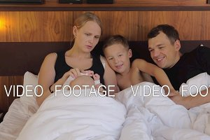 Happy parents with children lying in bed together