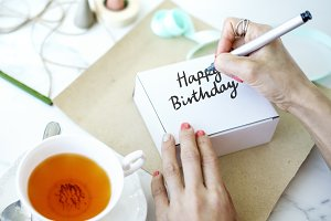 Woman writing Happy Birthday