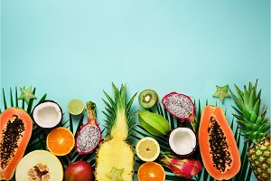 Exotic fruits and tropical palm leaves on pastel turquoise background - papaya, mango, pineapple, banana, carambola, dragon fruit, kiwi, lemon, orange, melon, coconut, lime. Top view.