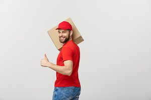 Cheerful young handsome delivery man holding a cardboard box and showing his thumb up while standing against grey background