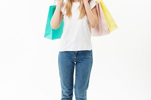 Full length portrait of a beautiful young woman posing with shopping bags, isolated on white background